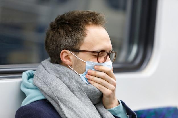 Hombre enfermo tosiendo, con máscara protectora en transporte público