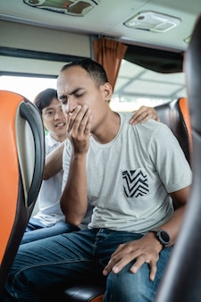 Un hombre enfermo de viaje y su amigo masajean su espalda mientras están sentados en un banco de autobús mientras viajan