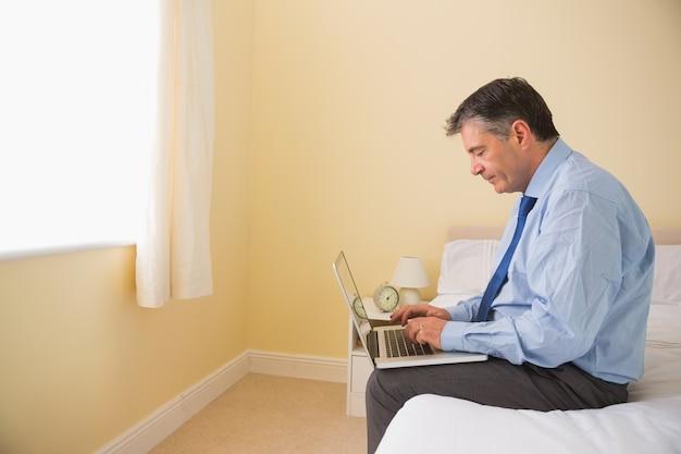 Hombre enfocado que usa una computadora portátil que se sienta en una cama
