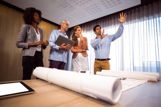 Hombre enmarcando con la mano mientras está de pie en la sala de juntas con colegas