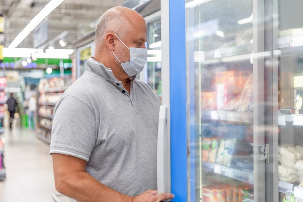 Un hombre enmascarado en un supermercado escoge alimentos congelados