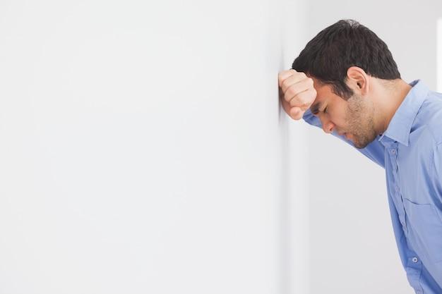 Hombre enojado apoyando su cabeza contra una pared