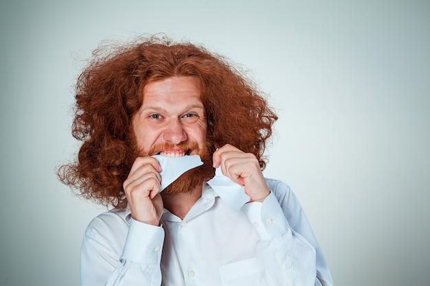 Hombre enojado arrancar papel