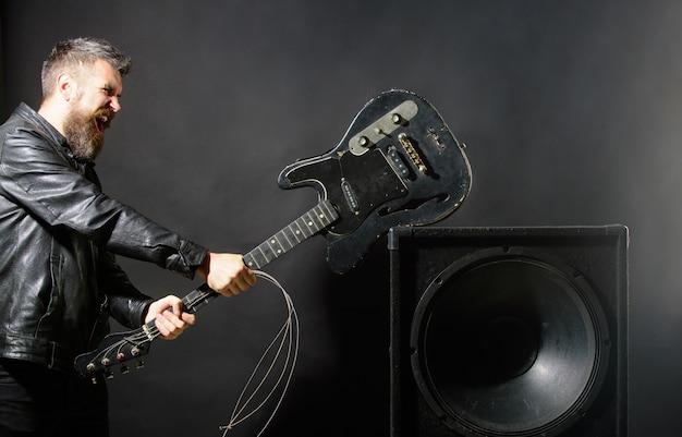 Hombre enojado con barba rompe guitarra en altavoces de música emociones agresión instrumentos musicales guitarra