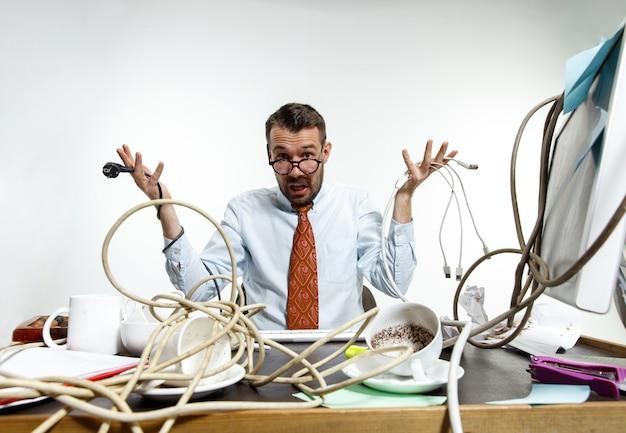 Hombre enojado con cables en su escritorio