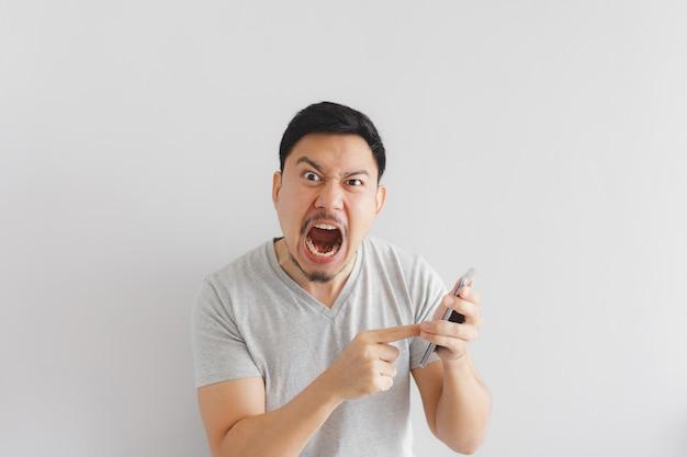 Hombre enojado con camiseta gris se enoja con el teléfono inteligente.