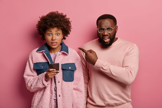 Un hombre enojado y disgustado con gafas señala a una mujer afroamericana con un teléfono inteligente que parece culpable y dice ¡ups !, adicta a las tecnologías modernas. pareja étnica posan juntos en el interior, siendo muy emocional