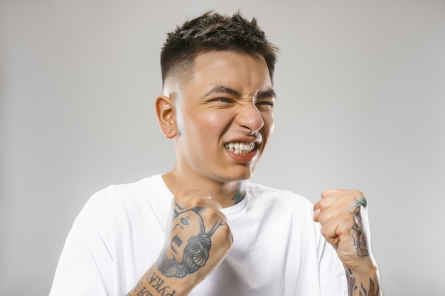 Hombre enojado emocional llorando gritando sobre fondo gris de estudio. rostro joven y emocional. retrato masculino de medio cuerpo. las emociones humanas, el concepto de expresión facial.