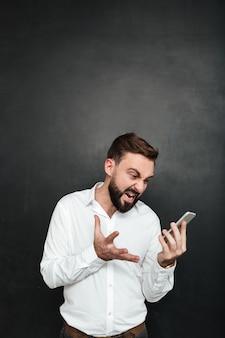 Hombre enojado gritando estar irritado mientras mira en el teléfono inteligente en su mano sobre gris oscuro