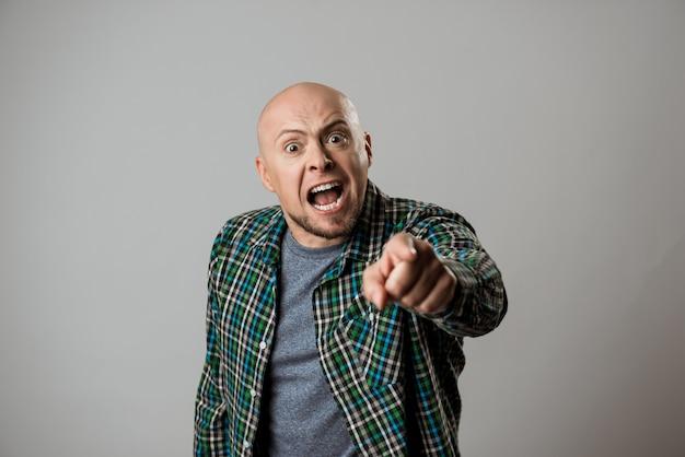 Hombre enojado gritando, señalando con el dedo sobre la pared de color beige.