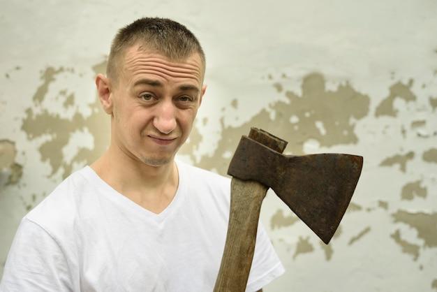 Hombre enojado con un hacha en la mano contra el telón de fondo de una pared en mal estado