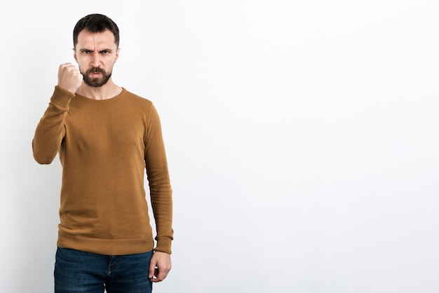 Hombre enojado posando con el puño arriba