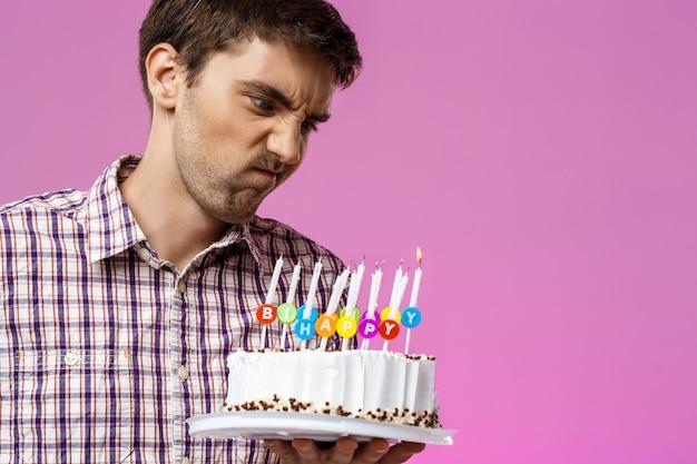 Hombre enojado que sostiene la torta de cumpleaños con una vela no apagada.