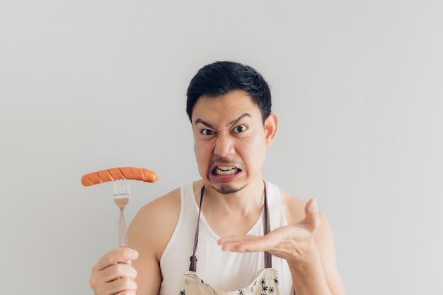 El hombre está enojado con la salchicha, ya que no es lo que esperaba para su dieta o no es delicioso.