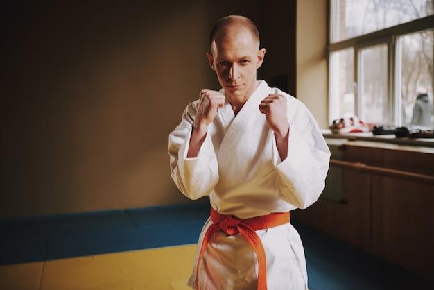 El hombre enseña técnicas de ataques de karate en el pasillo.