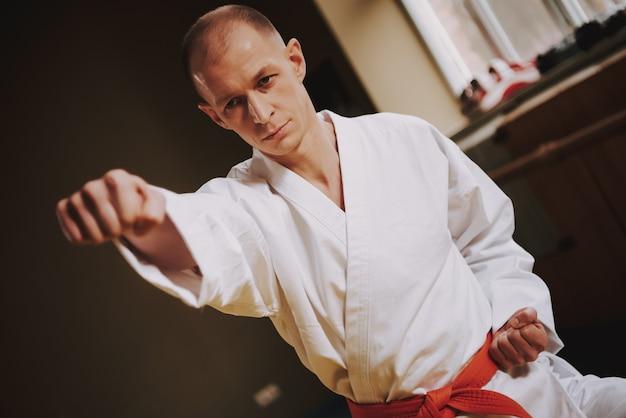 El hombre enseña técnicas de huelgas de judo en la sala.