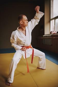 El hombre enseña técnicas de karate en la sala.