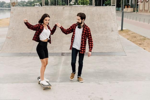 Hombre enseñando a novia a andar en patineta