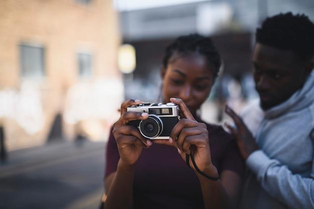 Hombre enseñando a su novia a usar una cámara de película vintage