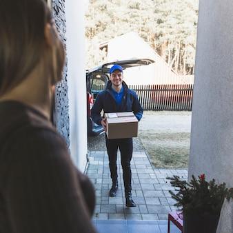 Hombre de entrega alegre que lleva la caja al cliente