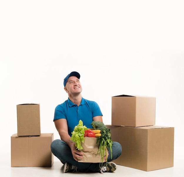Hombre de entrega con bolsa de supermercado mientras posa