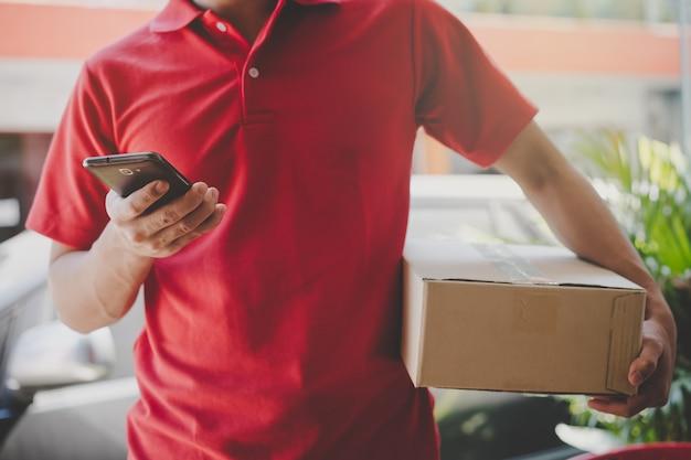 Hombre de entrega buscando la dirección del cliente en la aplicación móvil. enfoque selectivo en la mano.
