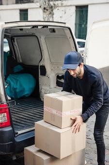 Hombre de entrega con cajas de cartón cerca del vehículo