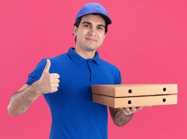 Hombre de entrega caucásico joven complacido en uniforme azul y gorra sosteniendo paquetes de pizza mostrando el pulgar hacia arriba