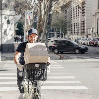 Hombre de entrega cruzando la calle en bicicleta con paquete