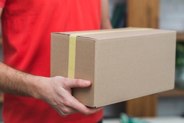 Hombre de entrega de cultivos con caja de cartón