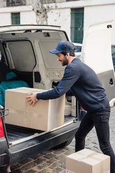 Hombre de entrega eliminando el paquete del vehículo