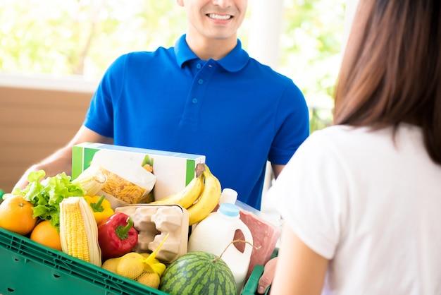 Hombre de entrega entregando alimentos a una mujer en casa