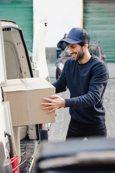 Hombre de entrega feliz que descarga el paquete del vehículo