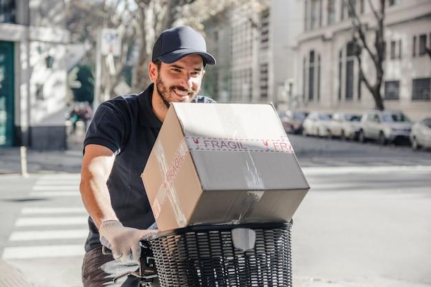 Hombre de entrega feliz que entrega el paquete en la bicicleta