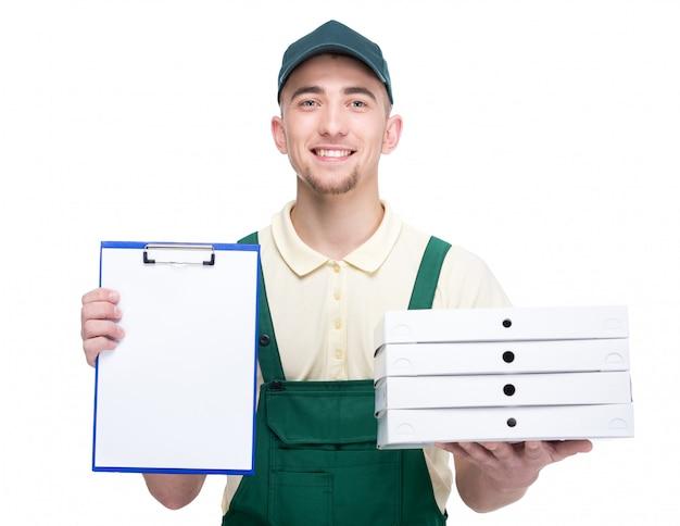 El hombre de entrega joven sonriente está sosteniendo las cajas de una pizza.