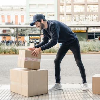 Hombre de entrega llevando parcela cerca de la calle