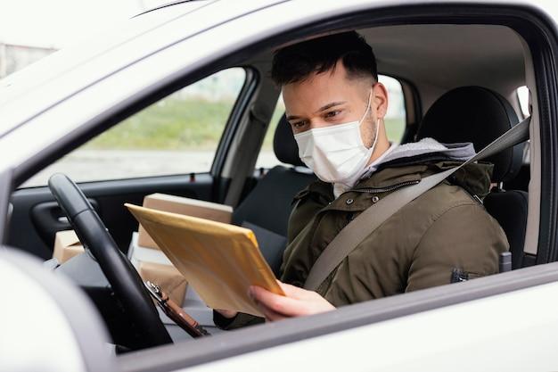 Hombre de entrega con máscara y paquetes