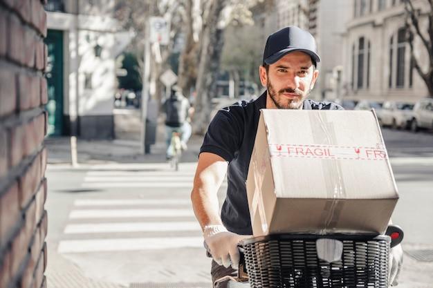 Hombre de entrega montando bicicleta con paquete