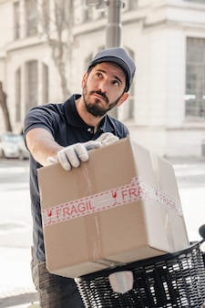 Hombre de entrega con paquete mirando hacia otro lado