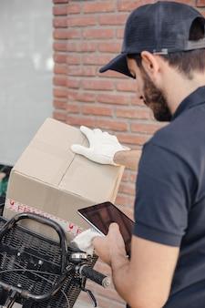 Hombre de entrega con paquete usando tableta digital