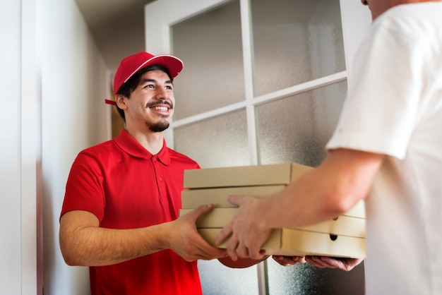 Hombre entrega pizza al cliente