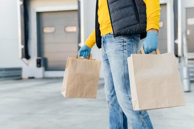 Hombre de entrega de primer plano sosteniendo bolsas de papel