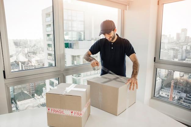 Hombre de entrega que embala la caja de cartón