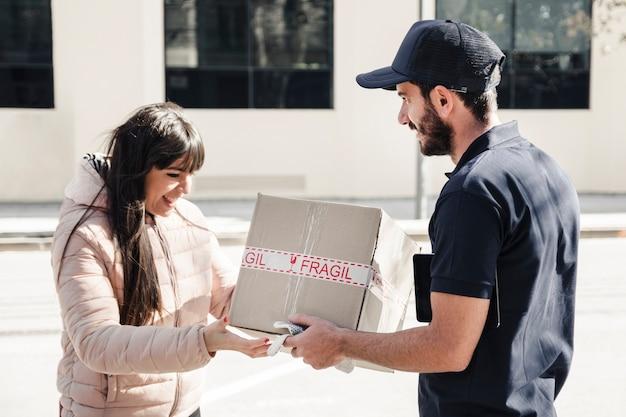 Hombre de entrega que entrega el paquete al cliente femenino