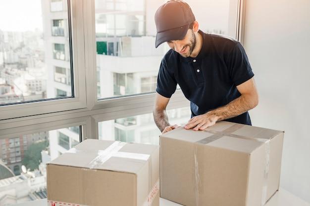 Hombre de entrega que prepara el paquete para el envío a los clientes