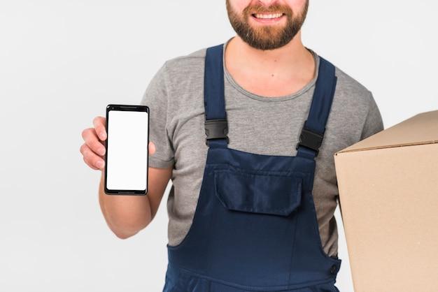 Hombre de entrega que sostiene la caja grande y el teléfono inteligente con pantalla en blanco