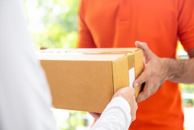 Hombre de entrega de servicio de mensajería dando caja de paquete al cliente