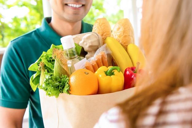 Hombre de entrega sonriente que da la bolsa de supermercado al cliente de la mujer en casa para el concepto de servicio de compra de alimentos en línea