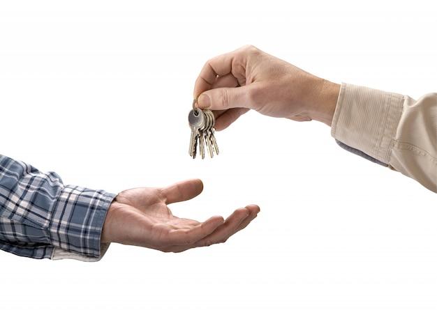 El hombre está entregando la llave de una casa a otro hombre.