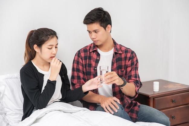 Un hombre entregó un medicamento a una mujer enferma en la cama.